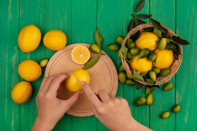 Bovenaanzicht van vrouwelijke handen verse citroen snijden op een houten keuken bord met mes met citroenen op een emmer op een groene houten muur