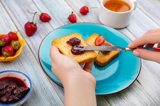 Bovenaanzicht van vrouwelijke handen verspreiden aardbeienjam op brood met mes over een blauwe schotel met verse aardbeien op een gele kom op een grijze houten achtergrond