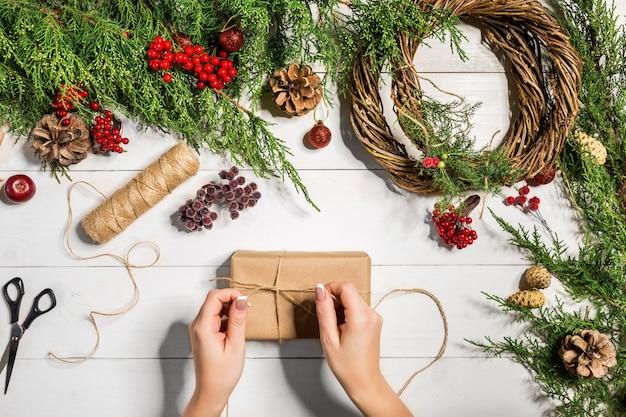 Bovenaanzicht van vrouwelijke handen wikkelen nieuwjaarscadeau verpakte geschenken en rollen vuren takken en gereedschap op...