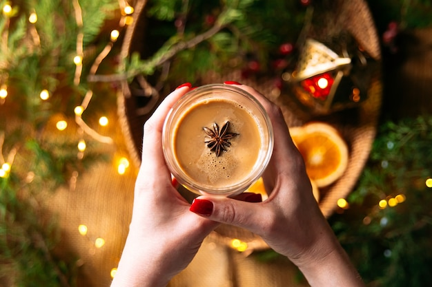 Bovenaanzicht van vrouwelijke hans die koffie latte met steranijs met feestelijke slingerachtergrond houden