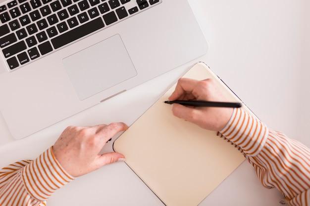 Bovenaanzicht van vrouwelijke leraar iets schrijven en laptop gebruikt tijdens online les
