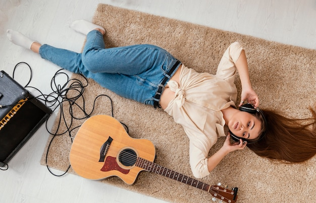 Bovenaanzicht van vrouwelijke muzikant op de vloer thuis met koptelefoon en akoestische gitaar