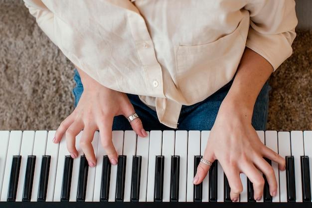 Bovenaanzicht van vrouwelijke muzikant pianotoetsenbord spelen