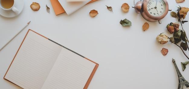 Bovenaanzicht van vrouwelijke vintage werkruimte met open notebook- en kantoorbenodigdheden
