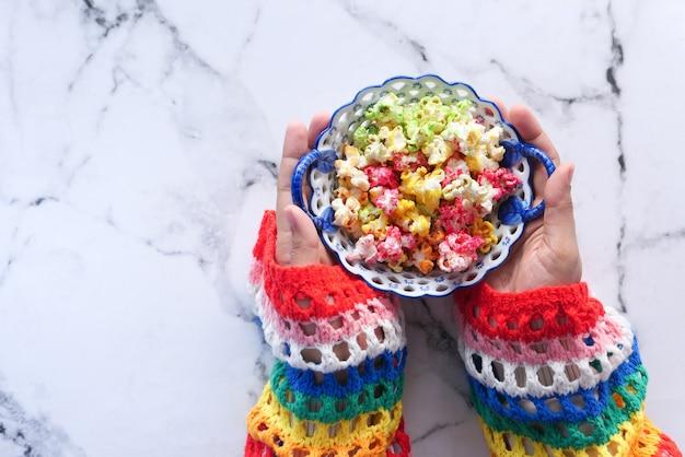 Bovenaanzicht van vrouwen hand met een kom kleurrijke popcorn.