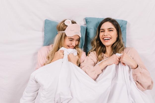 Bovenaanzicht van vrouwen lachen in bed