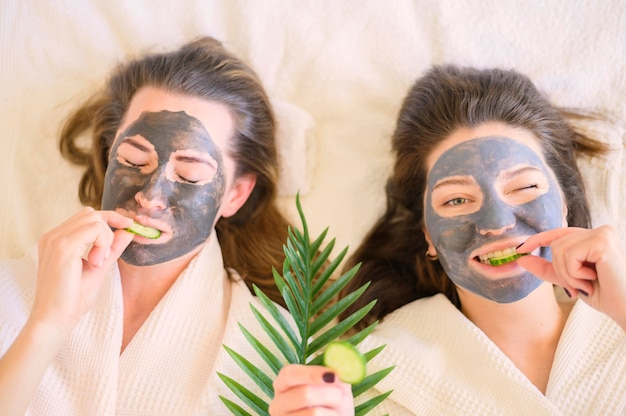 Bovenaanzicht van vrouwen met gezichtsmaskers die plakjes komkommer eten