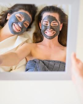 Bovenaanzicht van vrouwen met gezichtsmaskers in de spiegel kijken