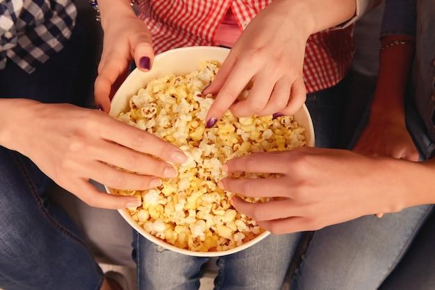 Bovenaanzicht van vrouwenhanden die popcorn nemen