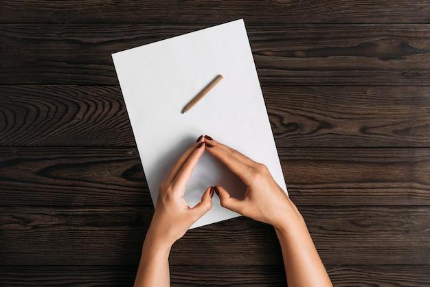 Bovenaanzicht van vrouwenhanden, klaar om iets op een leeg vel papier te schrijven