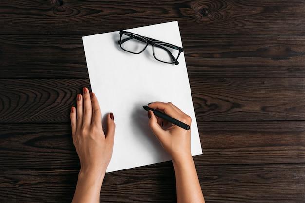Bovenaanzicht van vrouwenhanden, klaar om iets te schrijven op een leeg vel papier liggend op een houten tafel.
