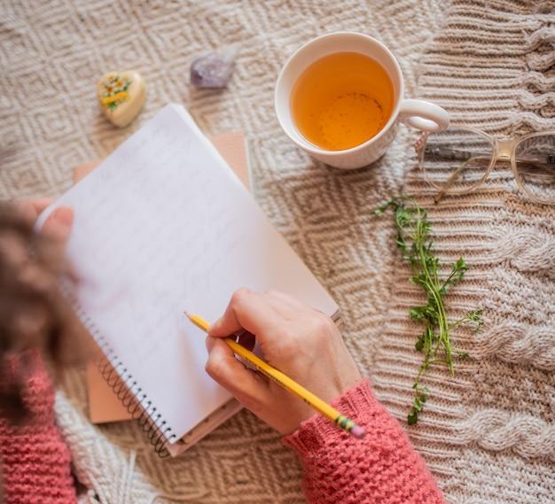 Bovenaanzicht van vrouwenhanden met een kopje thee schrijftafeltje