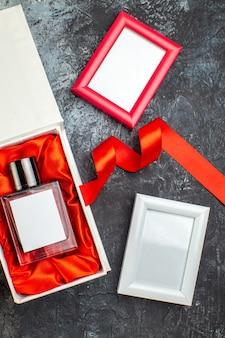 Bovenaanzicht van vrouwenparfum op geschenkdoos en fotolijstjes met blauw lint