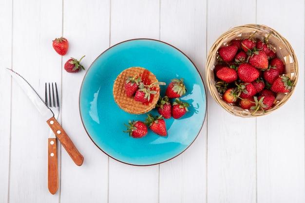 Bovenaanzicht van wafel koekjes en aardbeien in plaat en in mand met vork en mes op houten oppervlak