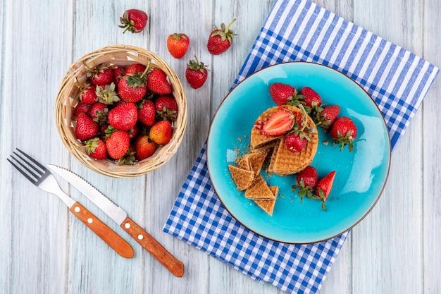 Bovenaanzicht van wafel koekjes en aardbeien in plaat en in mand met vork en mes op plaid doek en houten oppervlak