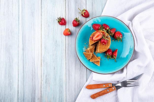 Bovenaanzicht van wafel koekjes en aardbeien in plaat met vork en mes op doek en houten oppervlak