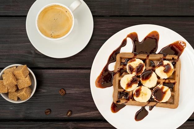 Bovenaanzicht van wafel met plakjes banaan gegarneerd met chocoladesaus