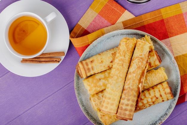 Bovenaanzicht van wafel roll gevuld met condens op een bord geserveerd met groene thee op houten paarse oppervlak