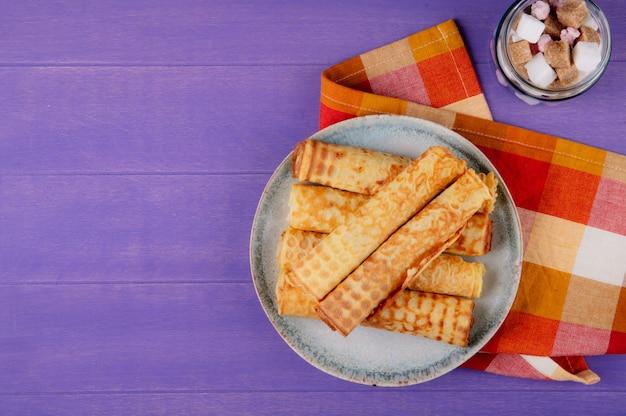 Bovenaanzicht van wafel roll gevuld met condens op een plaat en suikerklontjes in een glazen pot op houten paarse achtergrond