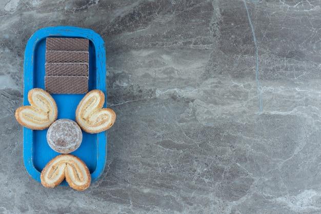 Bovenaanzicht van wafels en koekjes op blauwe houten plaat.