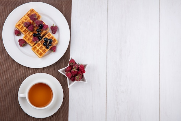 Bovenaanzicht van wafels op een bord met frambozen en een kopje thee op een wit oppervlak
