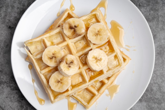 Bovenaanzicht van wafels op plaat met honing en banaan plakjes