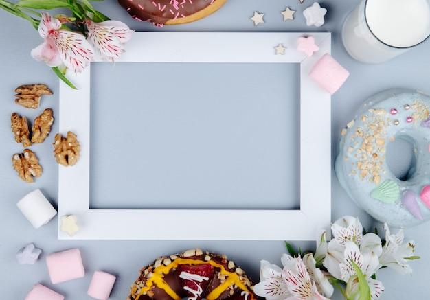 Bovenaanzicht van walnoten met snoepjes koekjes melk en bloemen op paars met kopie ruimte