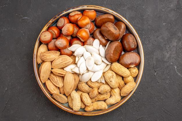 Bovenaanzicht van walnoten, pinda's, hazelnoten en anderen op een donkere ondergrond