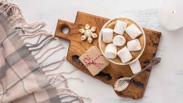 Bovenaanzicht van warme chocolademelk en marshmallows in beker met lepel en deken
