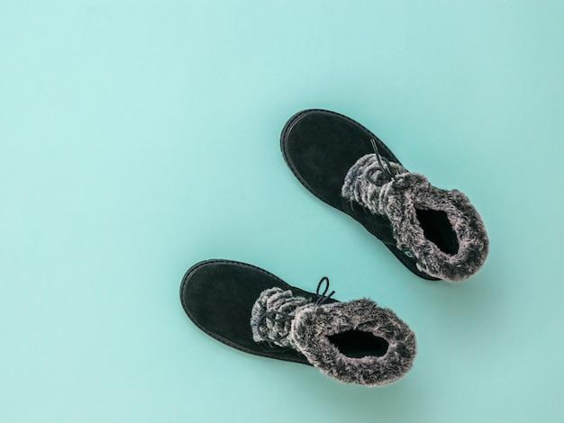 Bovenaanzicht van warme damesschoenen met bont op een blauwe achtergrond. mode stijlvolle dames winterlaarzen. plat leggen.