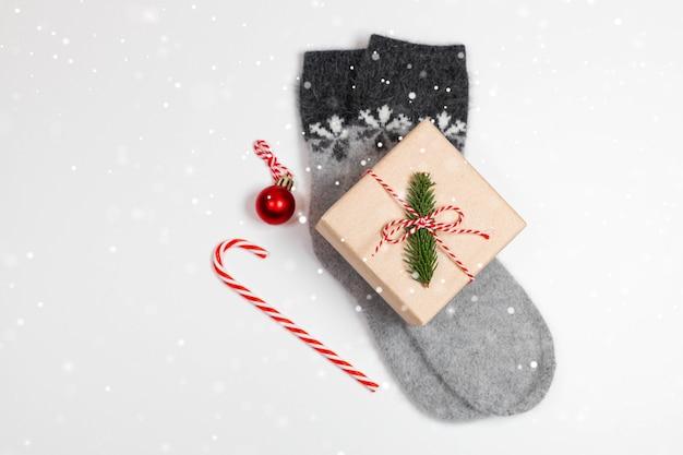 Bovenaanzicht van warme sokken met sneeuwvlokken, geschenkverpakking verpakt in kraftpapier en strik op grijze achtergrond. kerst minimale compositie met wazig licht
