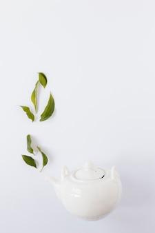 Bovenaanzicht van waterkoker met theebladeren