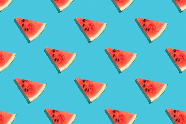 Bovenaanzicht van watermeloen plakjes op blauwe achtergrond. watermeloen kleurrijk patroon.