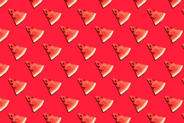 Bovenaanzicht van watermeloen plakjes op rode achtergrond. watermeloen kleurrijk patroon.