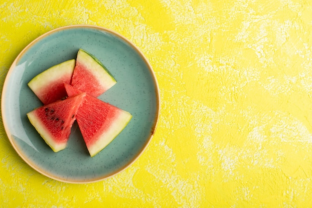 Bovenaanzicht van watermeloen plakjes zacht en zoet binnen groene plaat op het gele oppervlak