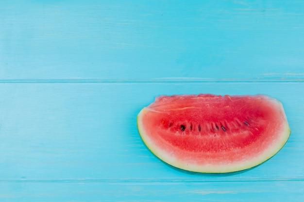 Bovenaanzicht van watermeloen segment op blauwe achtergrond met kopie ruimte