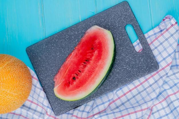 Bovenaanzicht van watermeloen segment op snijplank met hele meloen op geruite doek en blauwe achtergrond