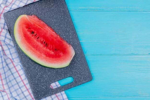 Bovenaanzicht van watermeloen segment op snijplank op plaid doek en blauwe achtergrond met kopie ruimte