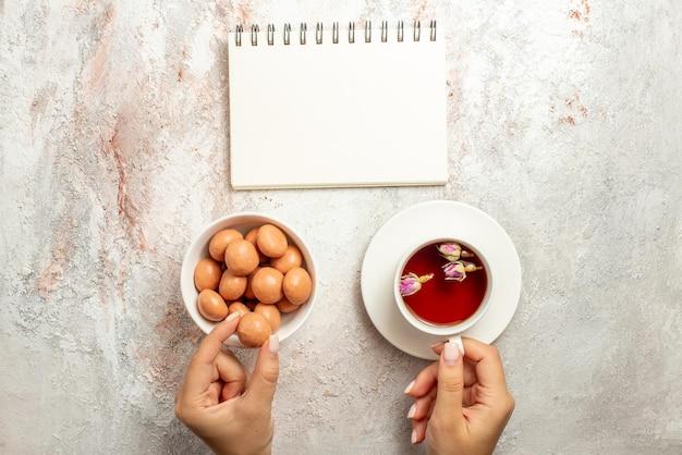 Bovenaanzicht van wegsnoepjes met een kopje thee wit notitieboekje naast de kom met snoep en een kopje thee in de hand op het witte oppervlak