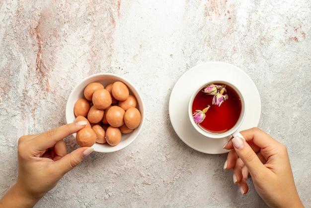 Bovenaanzicht van wegsnoepjes met een kopje theekom met snoep en een kopje thee in de hand op het witte oppervlak