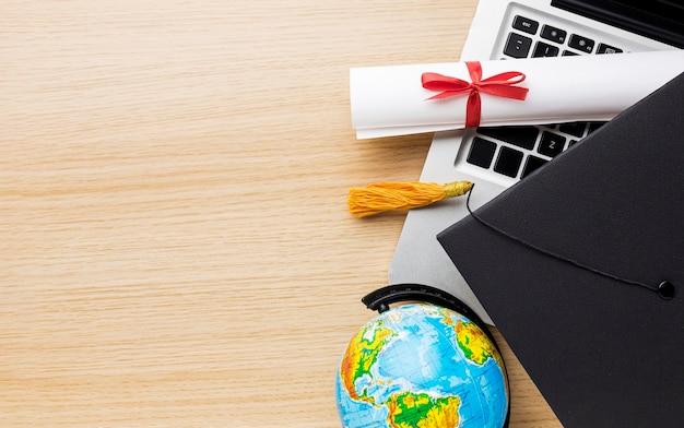 Bovenaanzicht van wereldbol met academische pet en laptop