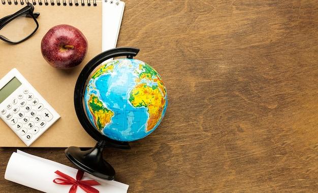 Bovenaanzicht van wereldbol met diploma en kopie ruimte