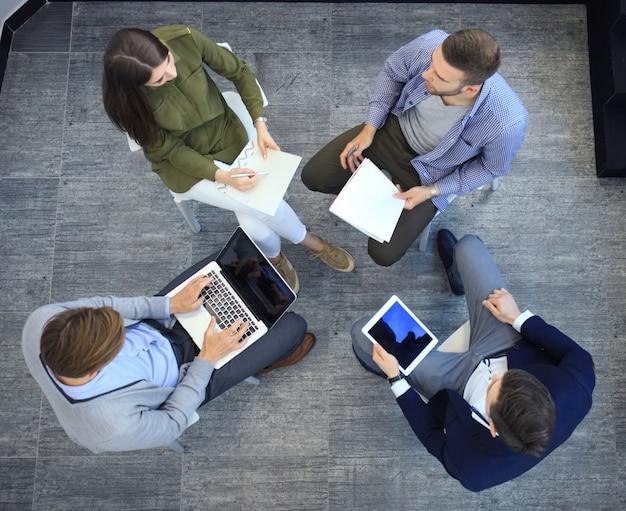Bovenaanzicht van werkende bedrijfsgroep zittend tijdens zakelijke bijeenkomst.