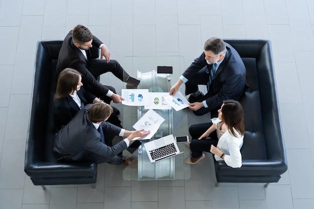 Bovenaanzicht van werkende businessgroep zittend aan tafel tijdens zakelijke bijeenkomst