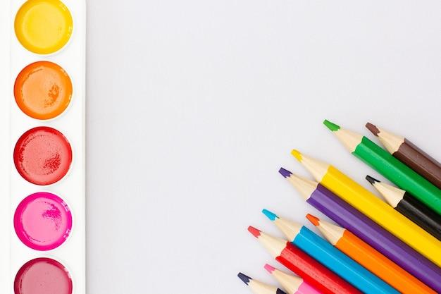 Bovenaanzicht van werkproces blanco aquarelpapier, aquarelverfbenodigdheden, penselen en kleurrijk potlood. creatieproces van aquarel schilderen. ruimte kopiëren.