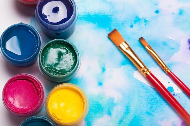 Bovenaanzicht van werkproces van aquarel papier pad, aquarel schilderij benodigdheden en penselen