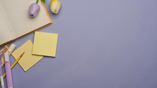 Bovenaanzicht van werkruimte met briefpapier, boek, bloem en kopie ruimte op paarse achtergrond