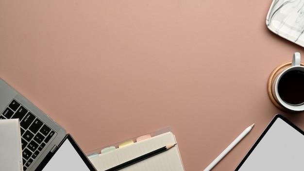 Bovenaanzicht van werkruimte met digitale apparaten, briefpapier, koffiekopje en kopie ruimte op roze tafel