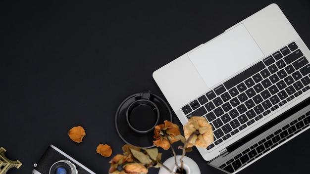 Bovenaanzicht van werkruimte met kopie ruimte, laptop, koffiekopje, camera en vaas op zwarte tafel
