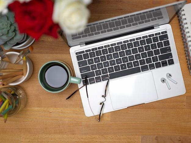 Bovenaanzicht van werkruimte met laptop, bril, koffiekopje en decoraties op houten tafel